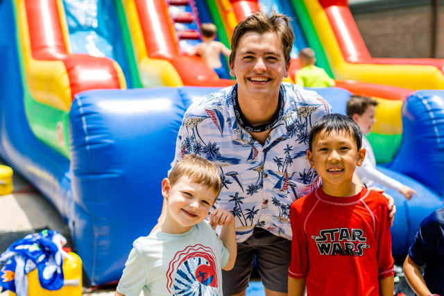Two City campers smile with their counselor in front of a giant inflatable water slide