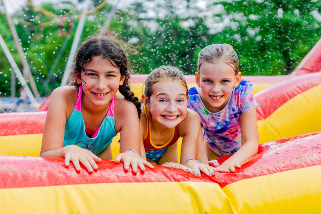 Three girls smile together on a water inflatable