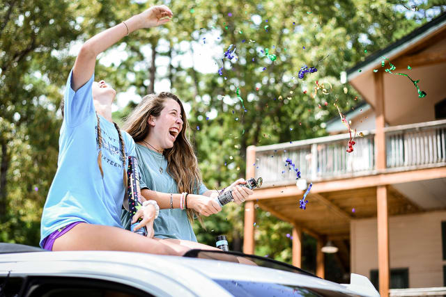 girls riding on car happy about confetti