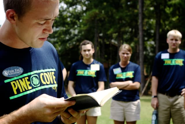 Pine Cove counselor reading the bible