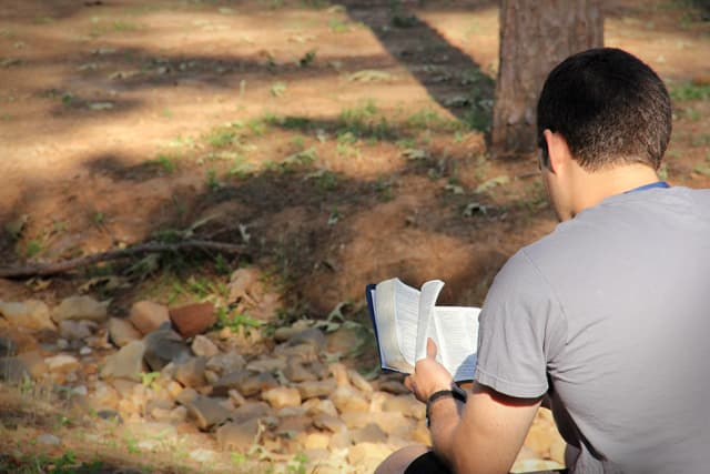 Guy Reading Bible At Camp