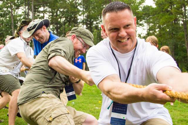 A group of men compete in a camp activity