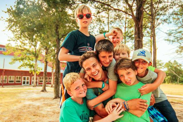 Campers piling on their camp counselor