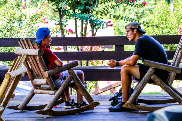A counselor has an intentional conversation with his camper while sitting in rocking chairs.
