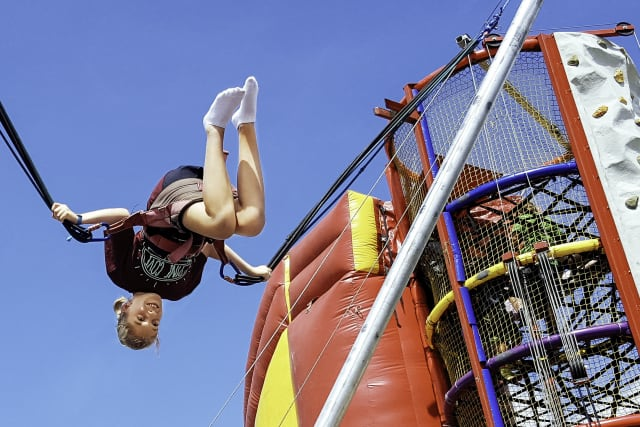 Girl flips upside down on a eurobungee, outside next to colorful inflatables and climbing walls.