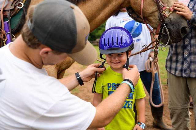 A counselor adjusts a helmet on a young boy before going horseback riding.