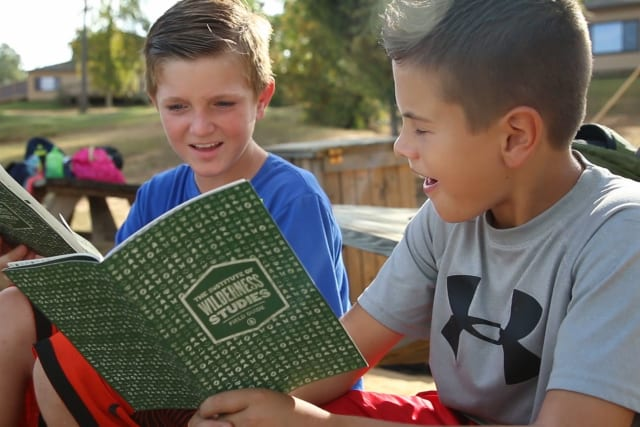 Two students sitting on a picnic table read their outdoor education field guide together.