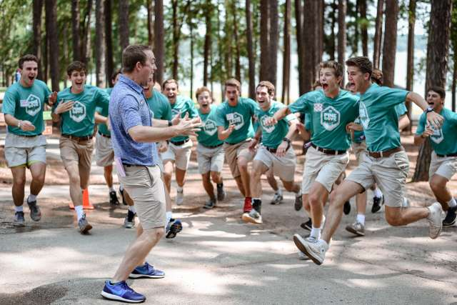 Energetic staff all run towards cheering man in the center