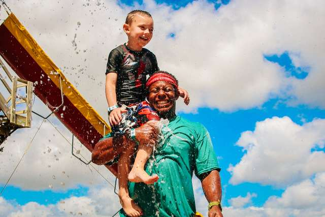Boy counselor holds up a camper on his shoulder as they get splashed by the water slide.