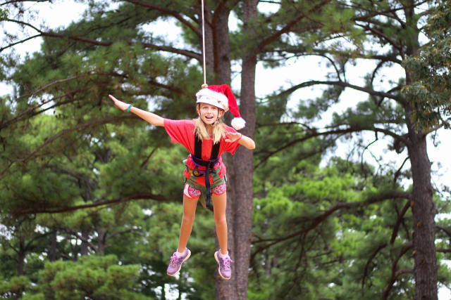 Girl wearing Santa hat on a ropes element