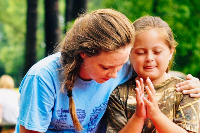 Counselor and camper praying together on a picnic table.