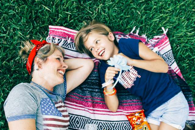 Mother and daughter smiling on a picnic blanket at family camp