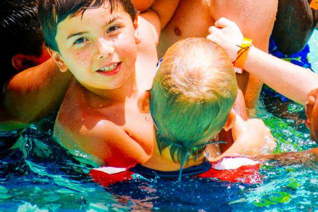 Boys playing in the pool with a camp counselor