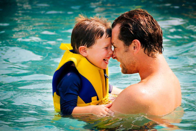 Father and son laughing and playing in the pool