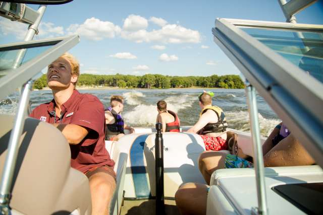 Boat driver and boat full of campers watch someone tubing