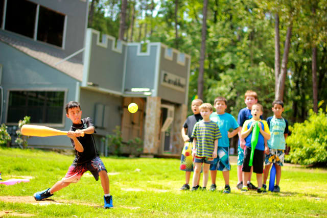 Elementary age boy campers play wiffleball at the Towers.