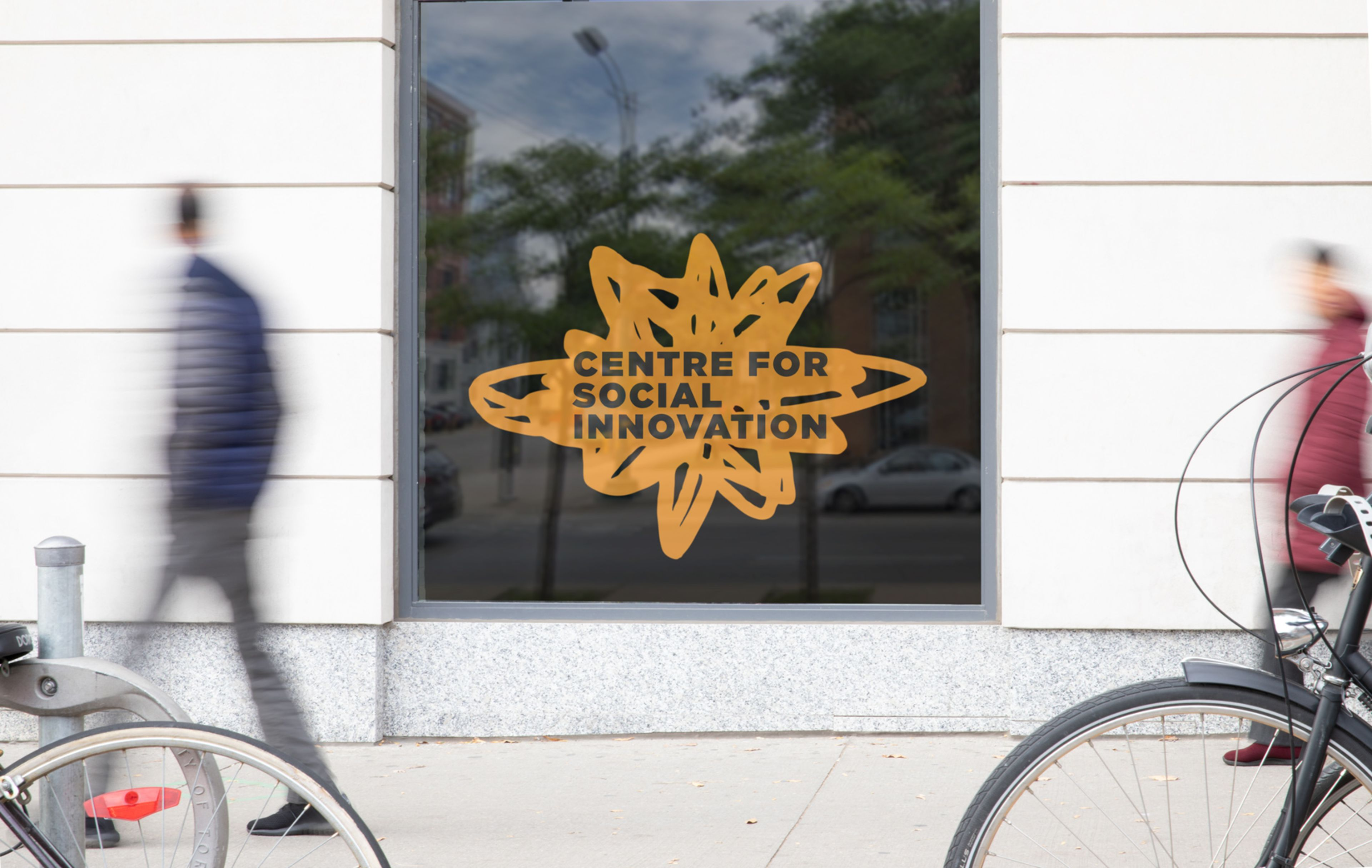 Centre for Social Innovation street-level branding on a window. In the reflection is busy Spadina Avenue in Toronto. People walking by, bikes locked up.