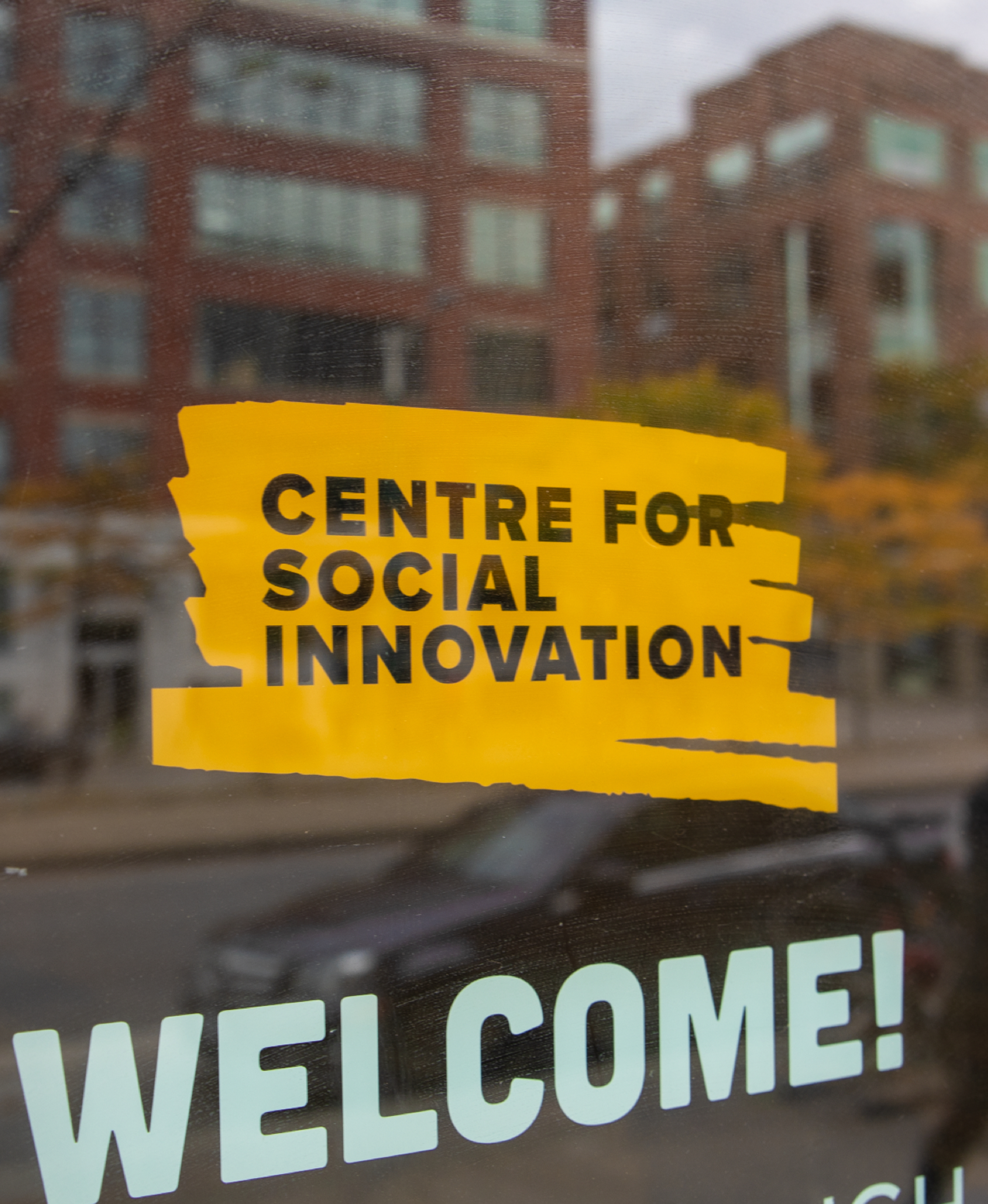 CSI Spadina street-level branding on the window and a 'WELCOME' message