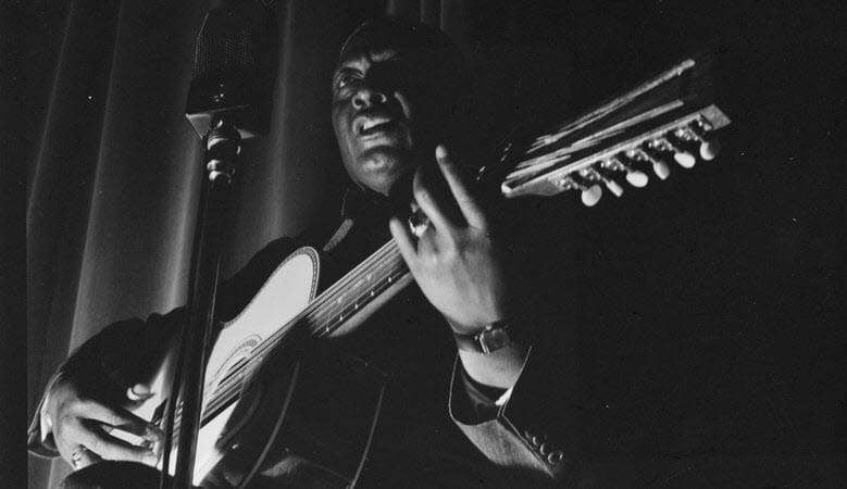Portrait of Lead Belly playing the guitar