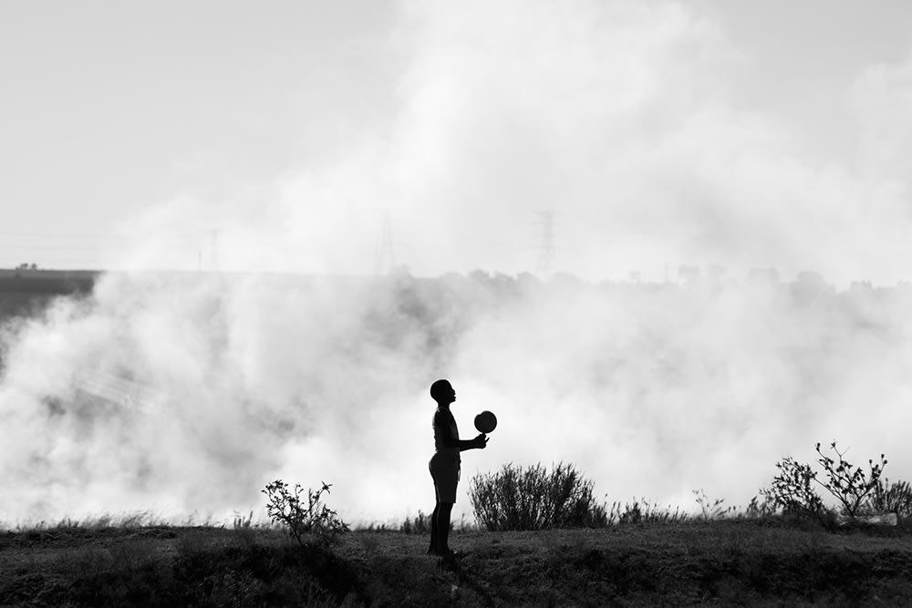 Child playing with ball near veld fire. Phola, Mpumalanga. 2018