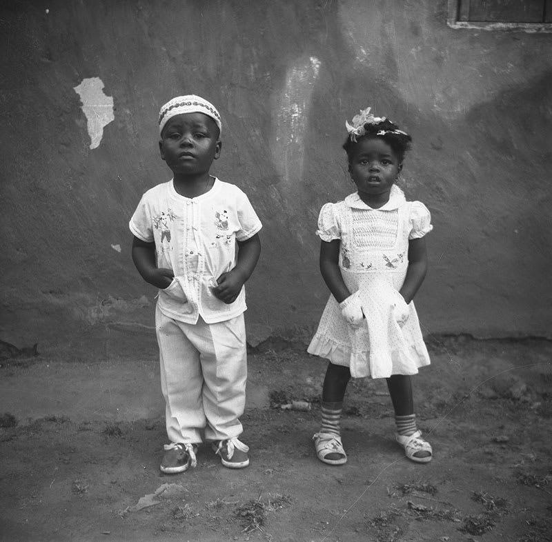 Photograph by Joseph Chila (b. Mbouda, Cameroon, 1948); Possibly the children of Al Haji Idrissu, a Bamum merchant from Foumban; 2021 inkjet print from digital scan of original undated negative.