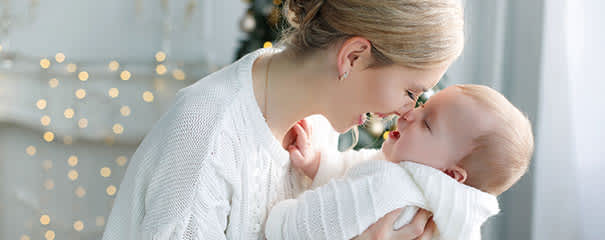 Mother holds baby in room decorated for Christmas