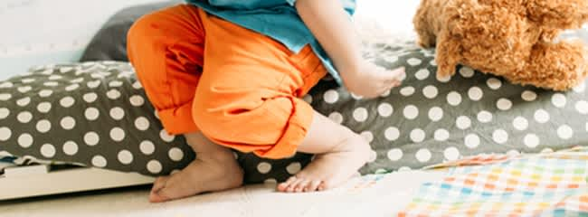 How can I help my 2-year-old adjust to a bed?