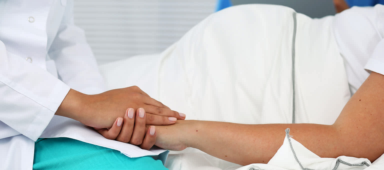 Nurse holding the hand of pregnant woman