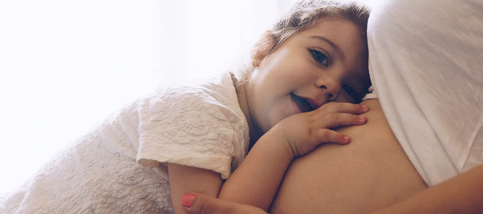 Toddler listens to pregnant mom's tummy