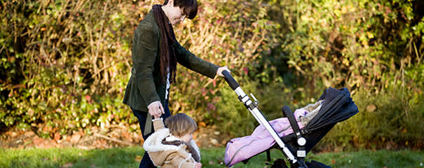 Mom walking outside with baby and toddler