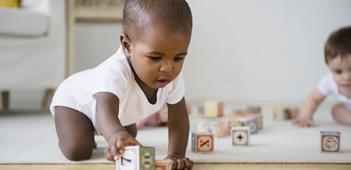 D-Toddler_wearing_a_babygro_playing_with_wooden_blocks