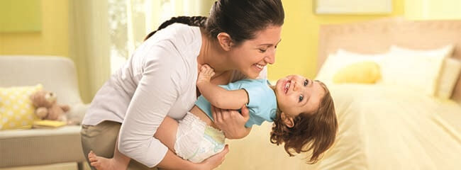 Smiling mother and toddler playing.