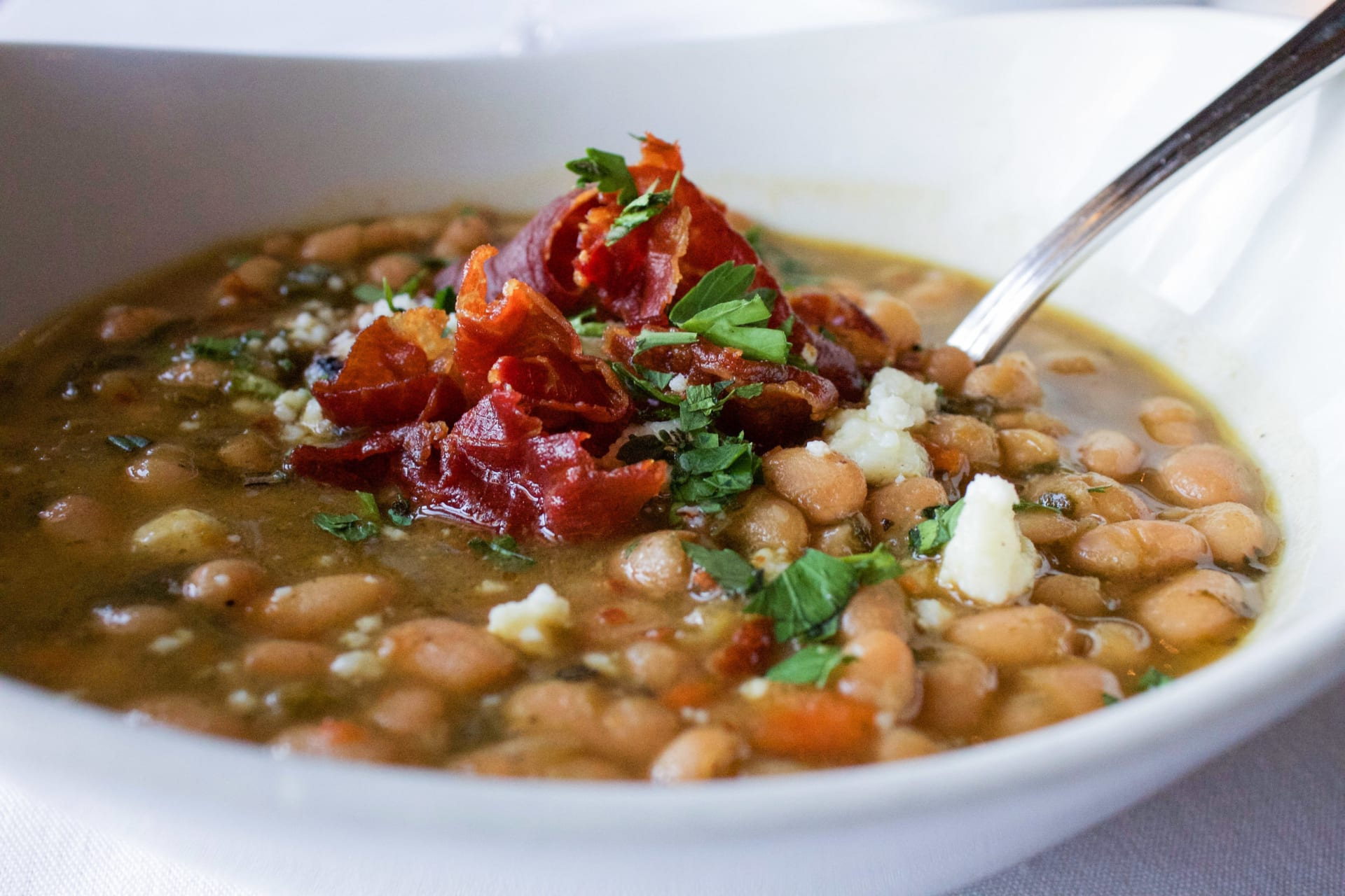 Close up of a Seasonal bean soup with a spoon