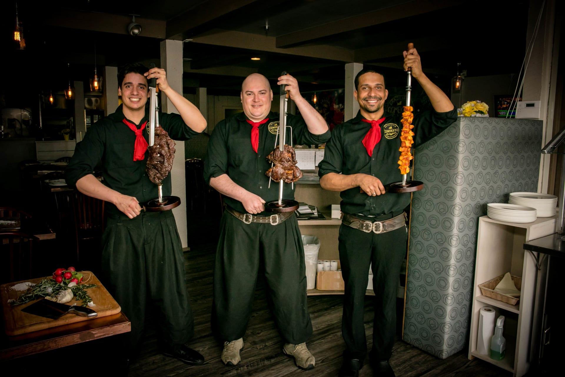 gauchos holding meat skewers