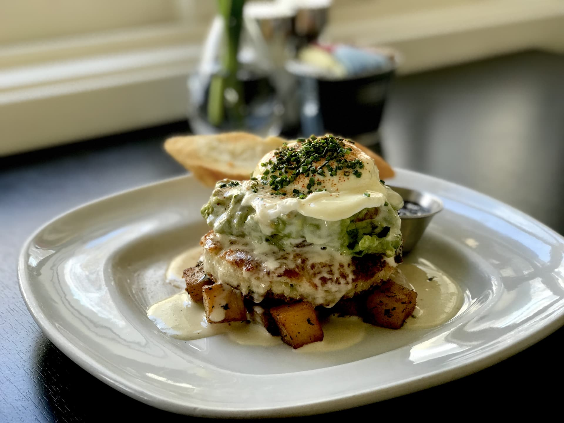 Dungeness Crab Cake & Potato Hash w/ Avocado Salsa,  Poached Egg, Beurre Blanc & Toast