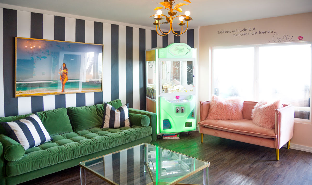 photo of green and pink couches and black and white striped wallpaper