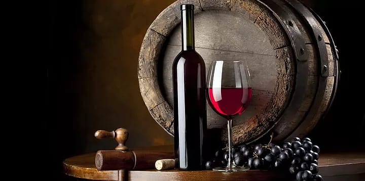 red wine in front of oak barrel