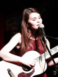 Hannah Murphy singing and playing the guitar