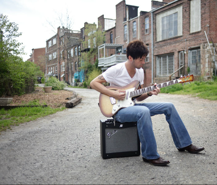Tony Sims playing an electric guitar while sitting on an amplifier