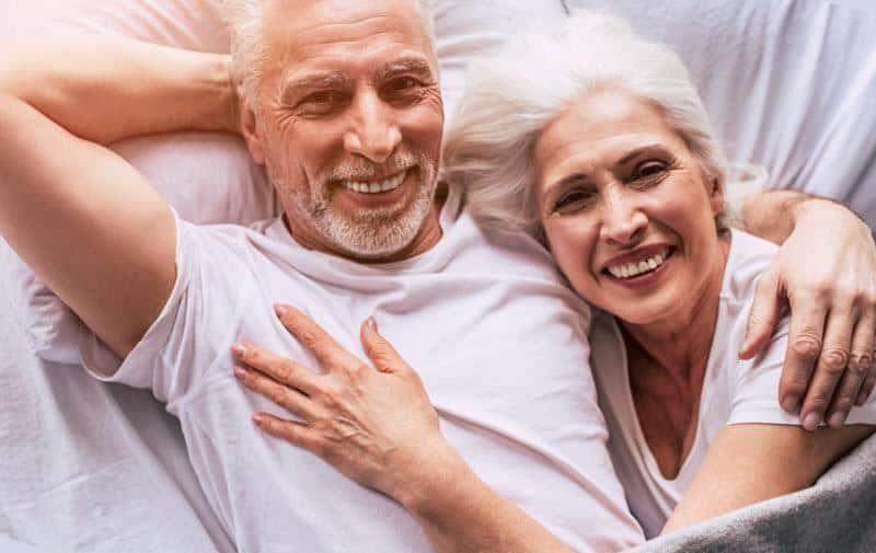 Cute Happy Elderly Couple In Bed