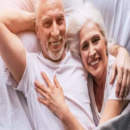 Cute Happy Elderly Couple In Bed