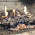Photo of log set with Holiday decor pieces to break up the flames.