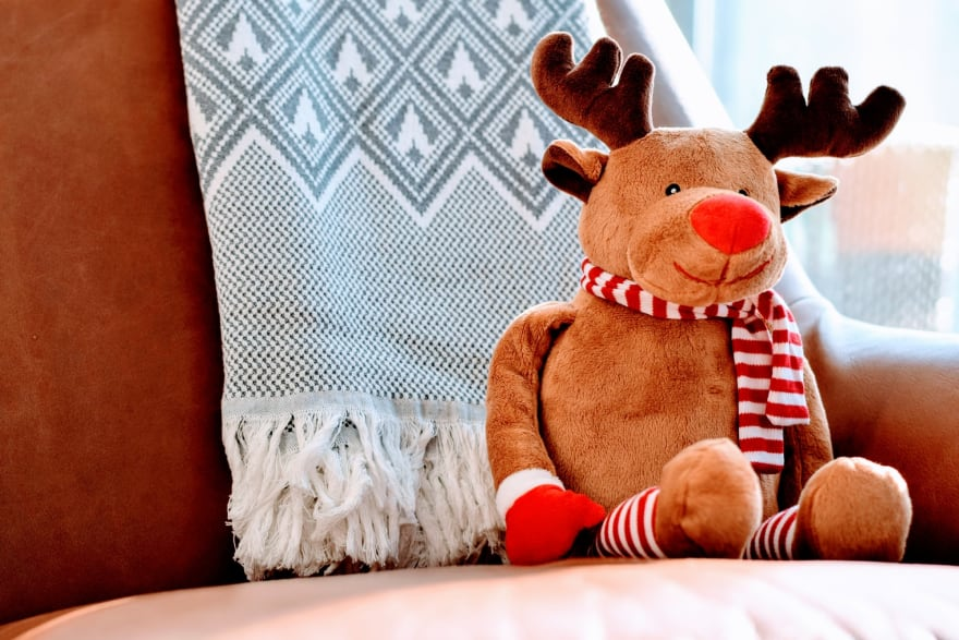 A stuffed reindeer sits on a plush chair