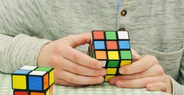 a male solving a Rubix cube
