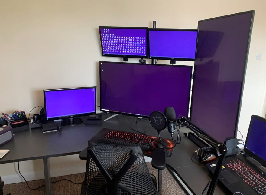 Home office - one 43 inch monitor horizontal as main, one 43 inch monitor in portrait at the side, two 21 inch monitors above main, 1 21 inch monitor to the left and a laptop to the right of everything. Microphone on moveable arm