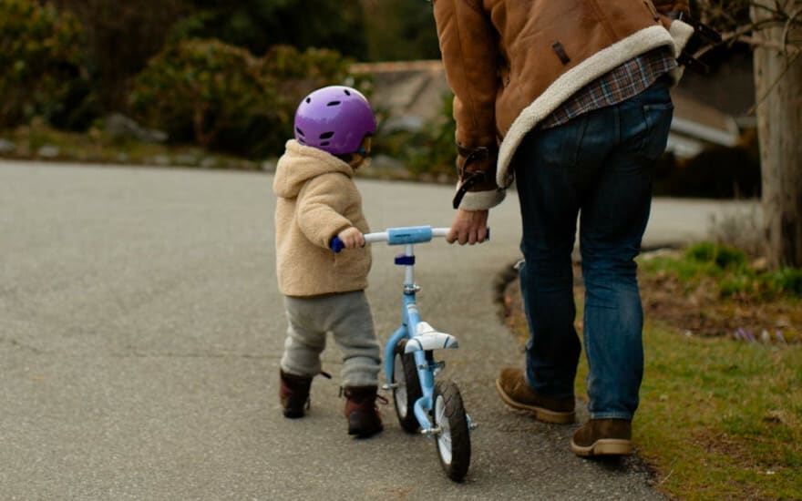 A little kid pushes a bicycle with the help of an adult