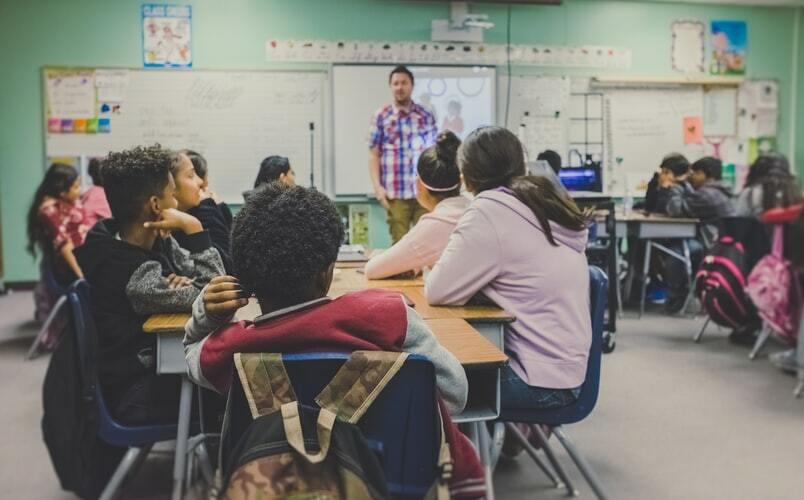 Students seated at a table in a classroom.  Image via Unsplash.