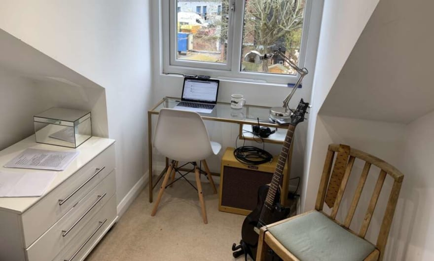 An example working from home desk with a chair and a guitar