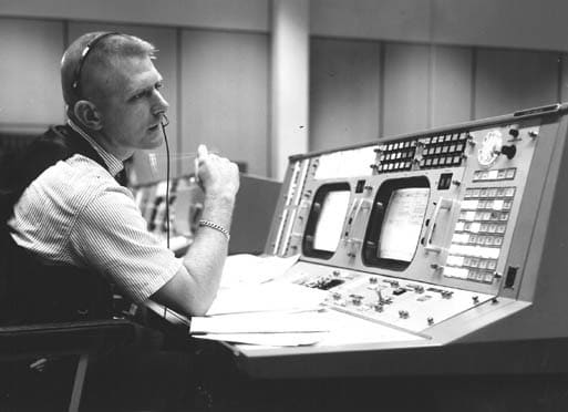 Black and white photo of Gene Kranz sitting at his desk in Mission Control
