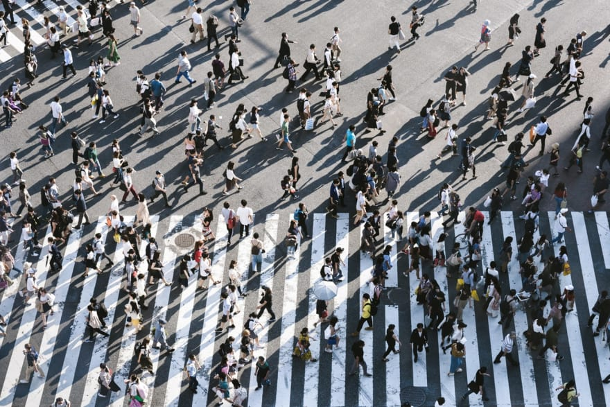 aerial view of a large cross walk with numerous pedestrians crossing